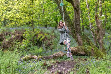 Tegan swinging on a rope swing surrounded by green leafy trees and bluebells underfoot.