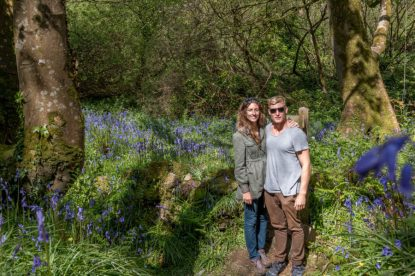 Couple shot in front of a beautiful area of bluebells, green contrasting with the bluebells in the forest as the sun streams through.
