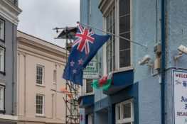 New Zealand flag next to a Welsh flag from a blue faced building.