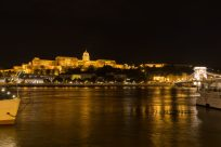 Parliament house lit up orange at night reflecting in the river danube