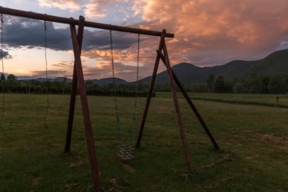 Sunset over a swing set with mountains int he background
