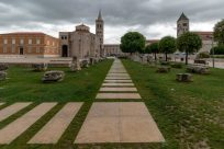 Green grass, long skinny pavers leading the way to the old buildings