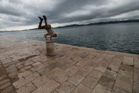 Dan doing a handstand on a limestone boat docking pole on the footpath