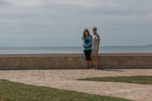 Tegan and Daniel standing next to the ANZAC plaque
