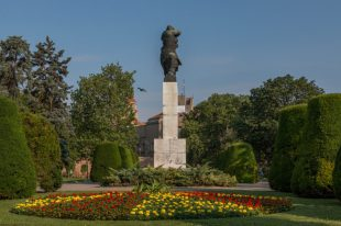 Big statue in the park, garden and flowers in the foregound, trees behind