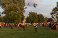 Polish festival, people dressed up throwing flags into the air to each other
