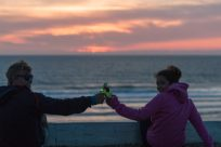 Two fellow surf lodge volunteers cheers beers with the sunset over the ocean in the background