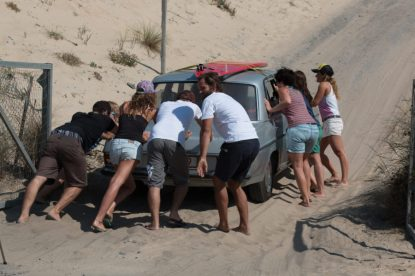 Gang from the surf hostel pushing a mercedes with no engine up the sand dune