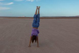 Tegan doing a wonky handstand on the salt flats