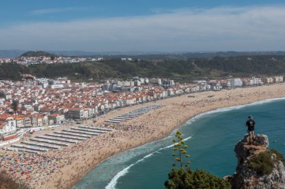 Looking over Nazare main beach from above, so many people and umbrellas