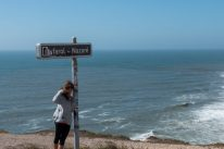 Tegan standing next to the sign for the famous Nazare lighthouse