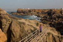 Tegan walking a wooden bridge along the cliffs