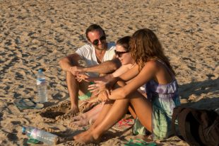 Tegan, Caitlin and Tony laughing on the beach