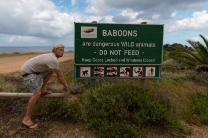 Dan pretending to be a baboon with his butt out of his shorts in front of the baboon sign