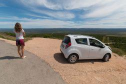 Tegan standing next to our tiny 4 door white car we took on safari