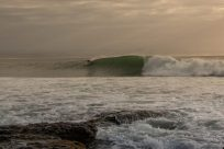 Sunlight streaming over a perfect untaken left hand wave at J Bay