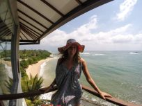 Tegs standing on the balcony overlooking the sea