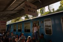 Tegs standing on the train with the Ella sign above