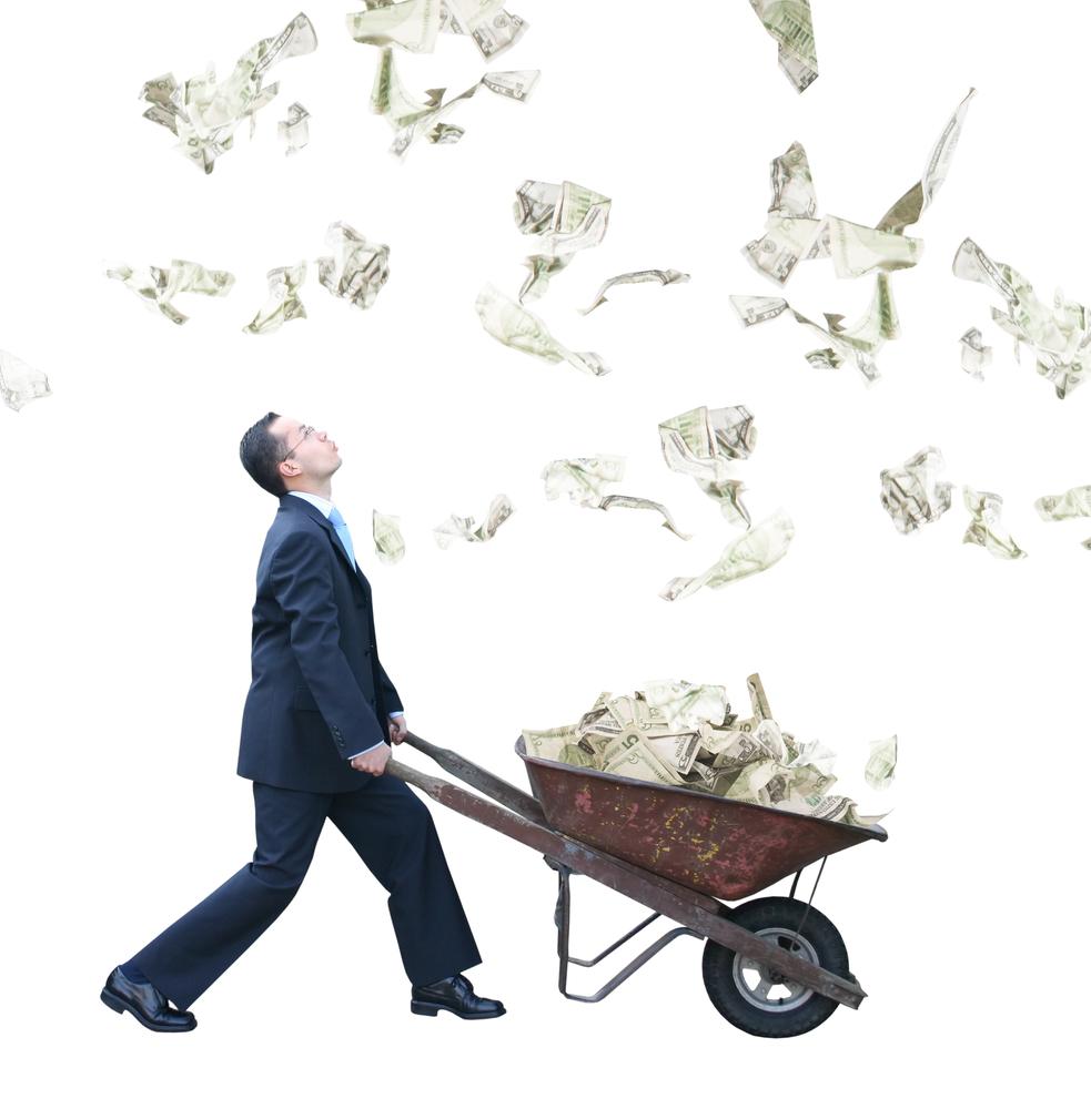 regner med pengesedler imens mand samler penge med trillebør
