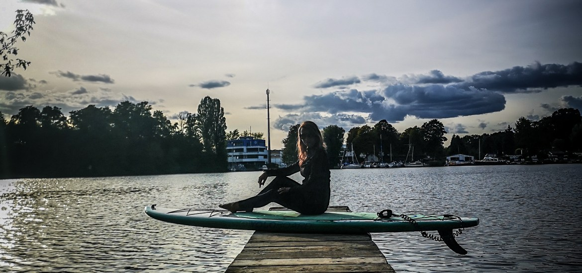 SUP Blogger sitting at the water on her hardboard
