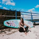 Stand up paddler sitting in front of her SUP Hardboard smiling