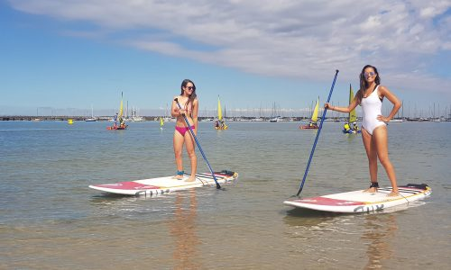 Girls posing on a stand up paddle board private lesson