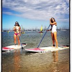 2 girl standing on paddle board after their hire