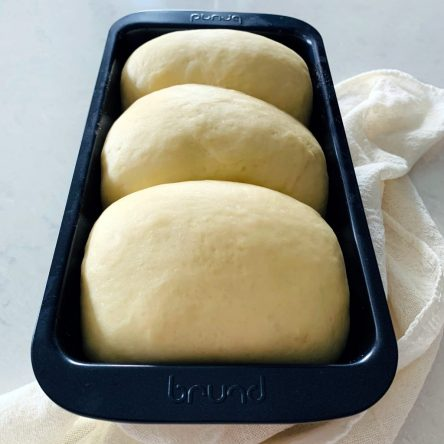 Three dough pieces fitted into a loaf pan, proofed and ready to be baked.
