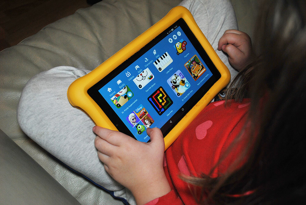 Kid playing Amazon fire tablet