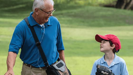 Elderly man on oxygen treatment walking with grandson