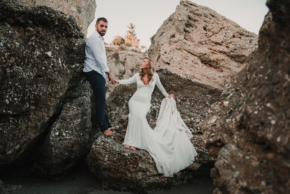 Novios apoyados en las rocas en las playas de Nerja, fotografía de postboda, Supercastizo