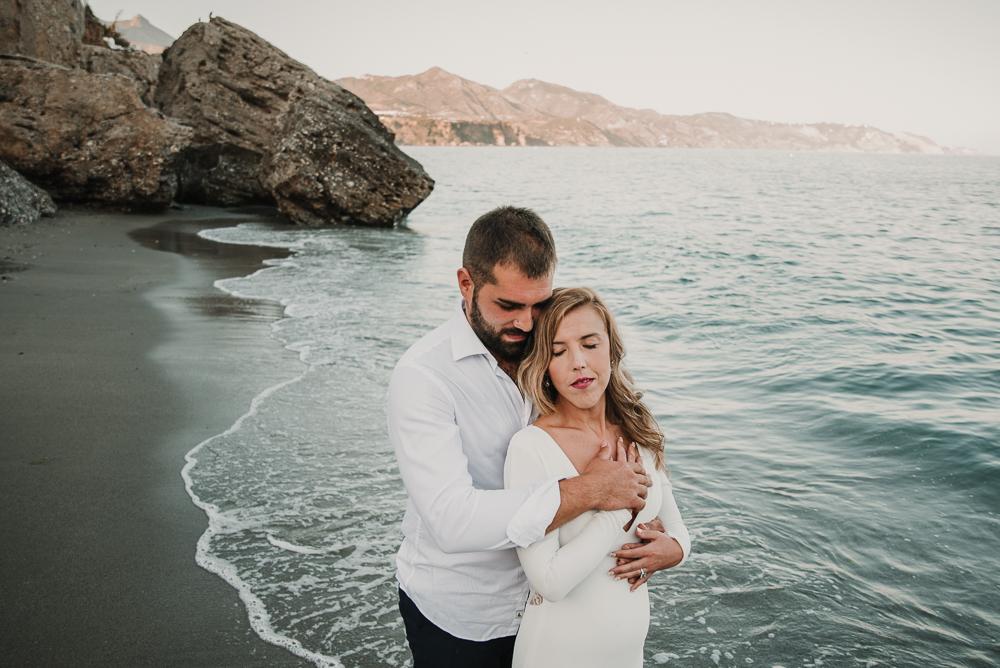 Novio abrazando a novia por detrás delante del mar en Nerja, fotografía de postboda, Supercastizo