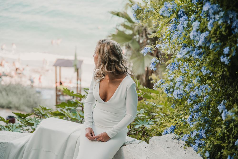 Novia sentada al lado de un macizo de flores mirando al mar en Nerja, fotografía de postboda, Supercastizo