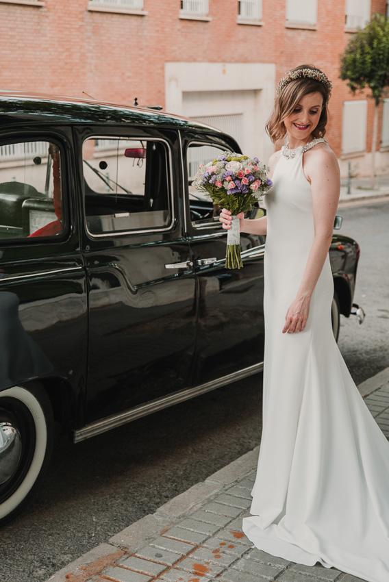 novia posando delante del coche