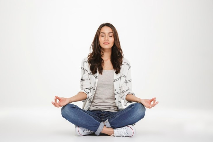 brunette woman casually meditating at home in converse mindfulness healthy living blendtopia
