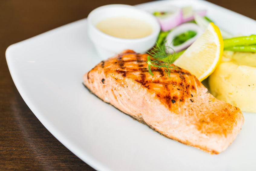 Photo of a plate with grilled salmon on it.