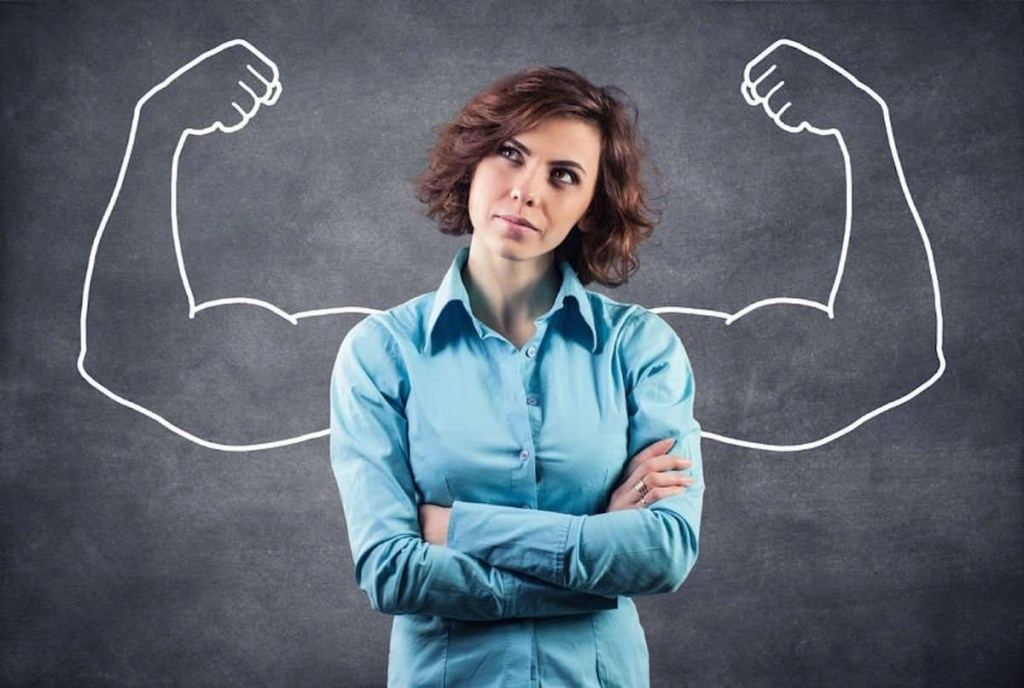 Photo of a woman, who seems to be mid-thought, looking upward, who is standing against a blackboard, and on the blackboard are drawn cartoonish, muscular arms posed to show off the big biceps. She is thinking big.