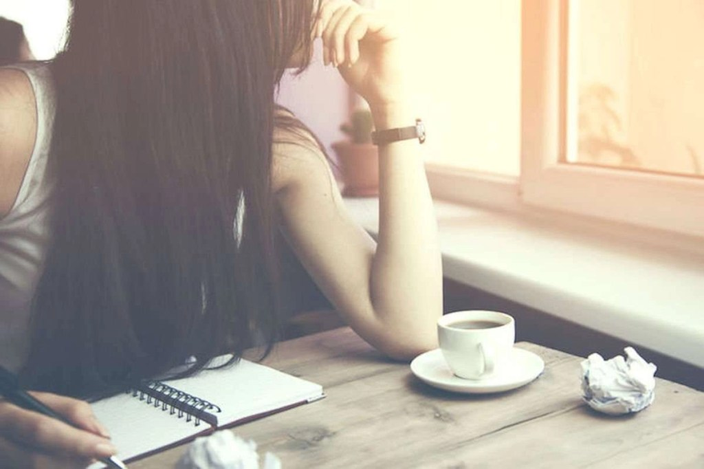 Photo of woman looking out of a window, contemplating, while taking notes with a pen in a notebook. There is a cup of espresso on the table and a balled-up piece of paper.