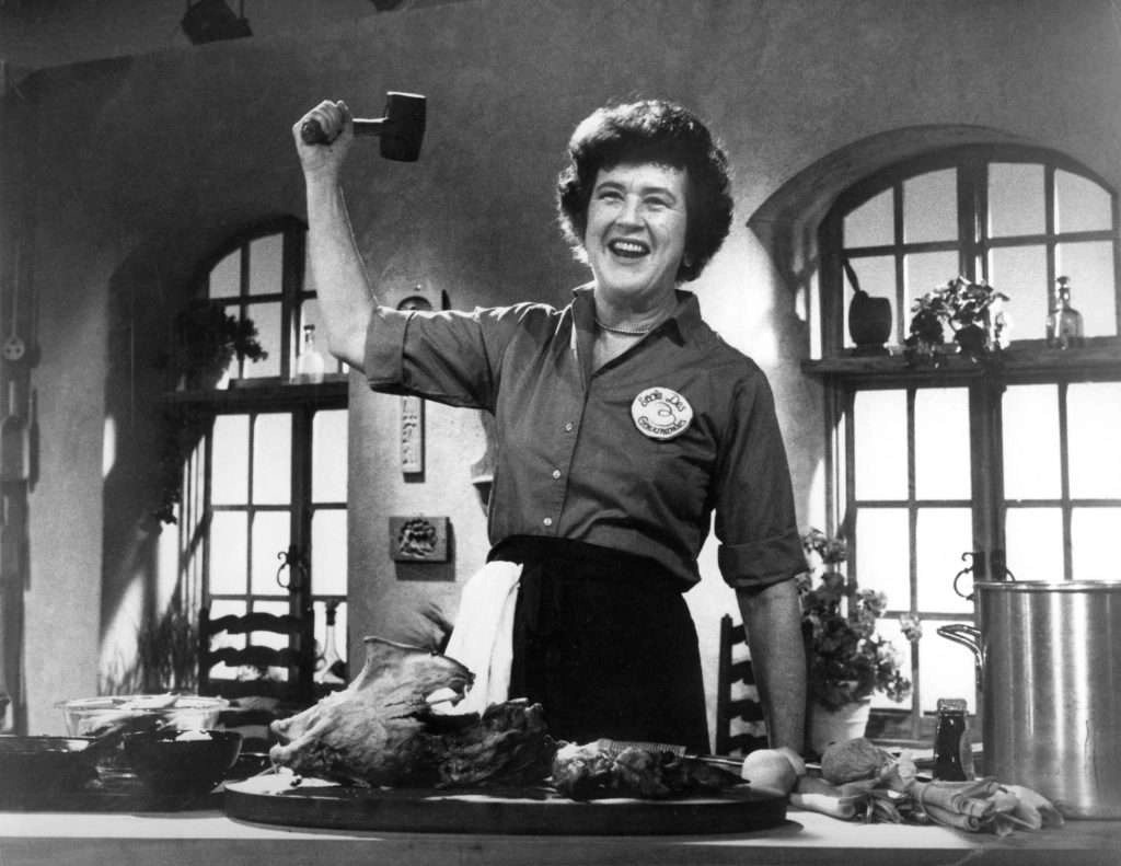 Still from an old TV show with Julia Child in a kitchen, gleefully holding a mallet in the air above a board of meat surrounded by vegetables and a big pot.