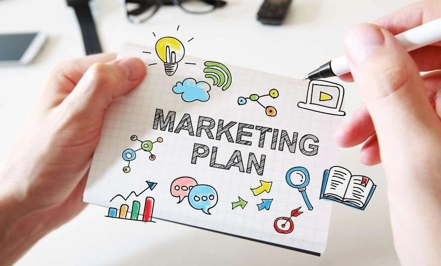 """Photo of a closeup of hands holding some sketches labeled """"Marketing Plan."""""""