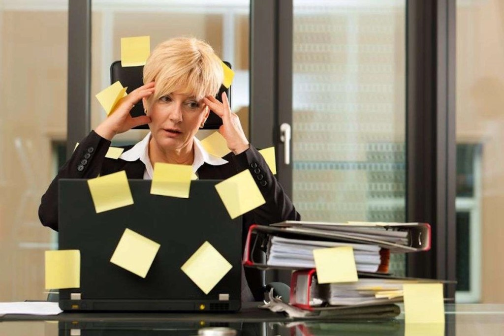 Photo of a stressed woman who is holding her hands to her forehead as if she has a headache, and there are yellow Post-It notes all over her laptop and the chair she is sitting on.