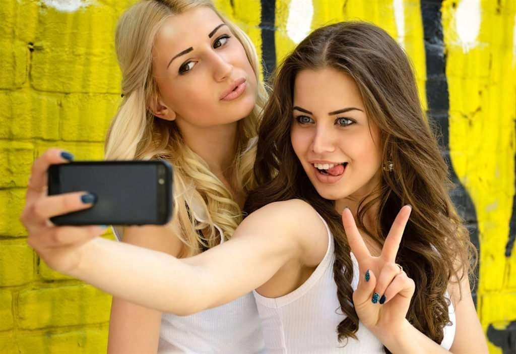 Two preening late-teenage girls hold up a  smartphone to take a selfie against a yellow graffiti wall.