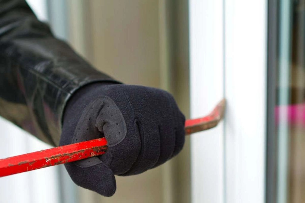Photo of a burglar wearing black gloves and a leather coat breaking into a house using a red crowbar.