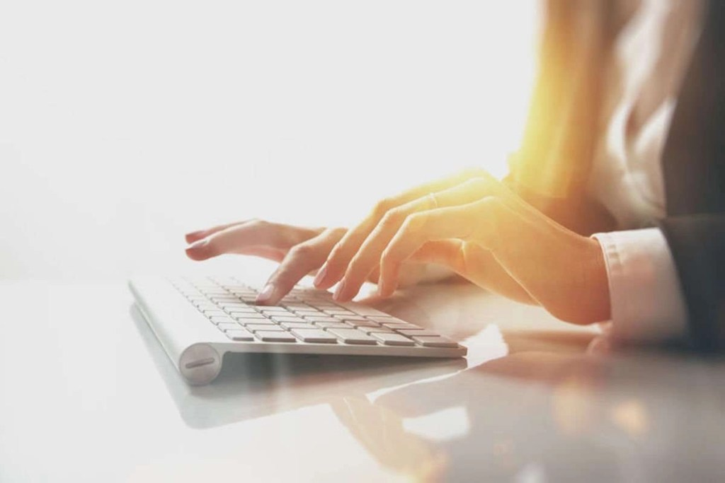 Closeup photo of a woman's hands typing text on a keyboard; there are visual lighting effects against a white background that make it look like the room is drenched in sunlight.