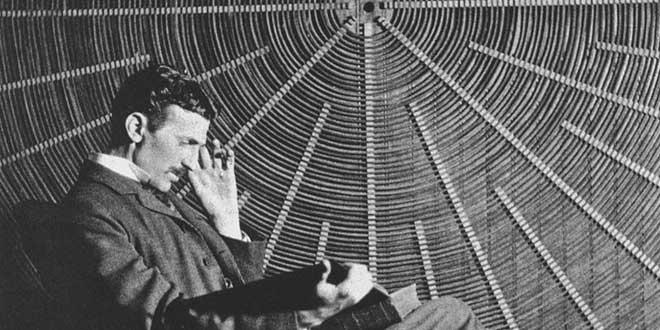 Nikola Tesla leyendo frente a la espiral de la bobina de su transformador de alta tensión en East Houston Street, Nueva York