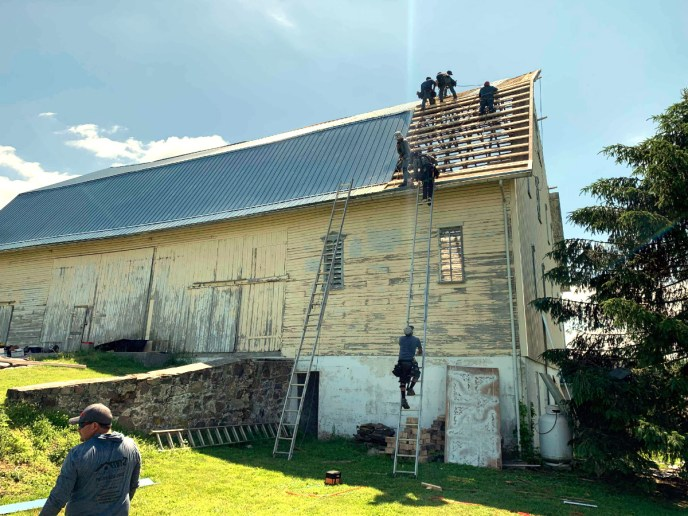 Expert metal roofing contractors hard at work installing the blue corrugated metal on this barn in Abbottstown PA 17301