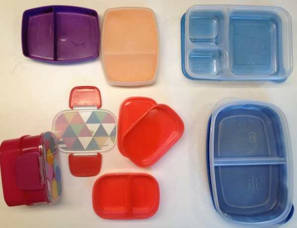 """Clockwise from upper left: our two Tupperware snack boxes, our Ziploc compartmentalized container, our Rubbermaid divided Serving Saver, and our two Target """"tiffin boxes."""""""