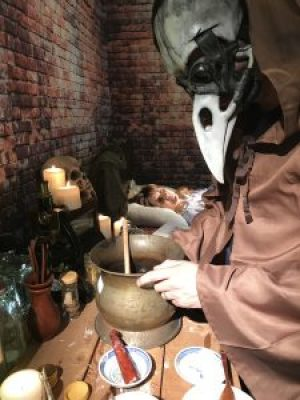 Photo from the film shoot for Cure or Be Cured showing the plague doctor with his patient