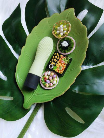 Iroha Zen Matcha on a green leaf plate next to tiny Japanese and Thai food figurines