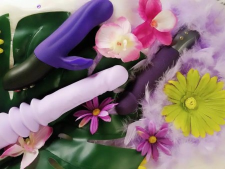 [Image: self-thrusting dildos! Purple Velvet Thruster Jackie, Fun Factory Stronic Real pulsator, and Bi Stronic Fusion among flowers and feathers]